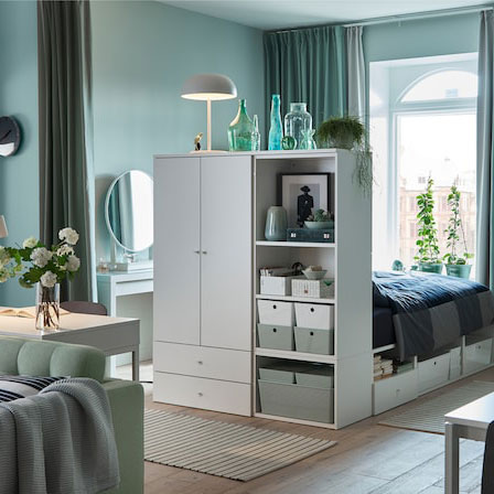 A calm and light green one-bedroom-apartment with green curtains, a green sofa and a white bed frame with storage.