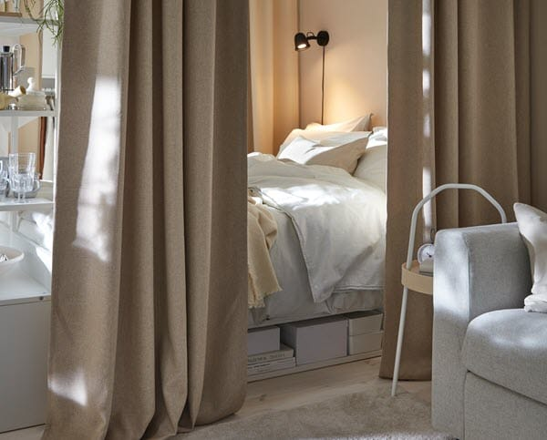 A calm bedroom with beige curtains and light coloured bedlinen.