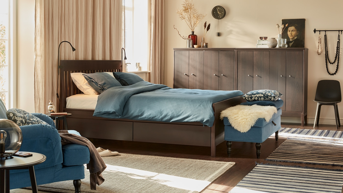 A calm bedroom with beige walls, linen curtains, wooden bed, dark blue textiles, bench, and wooden cabinets by the walls.