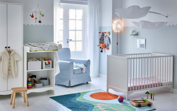 A calm blue and white nursery featuring the white SOLGUL cot, changing table and wardrobe.