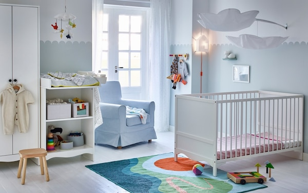 A calm blue and white nursery with a blue armchair, white SOLGUL cot, white changing table and white wardrobe.