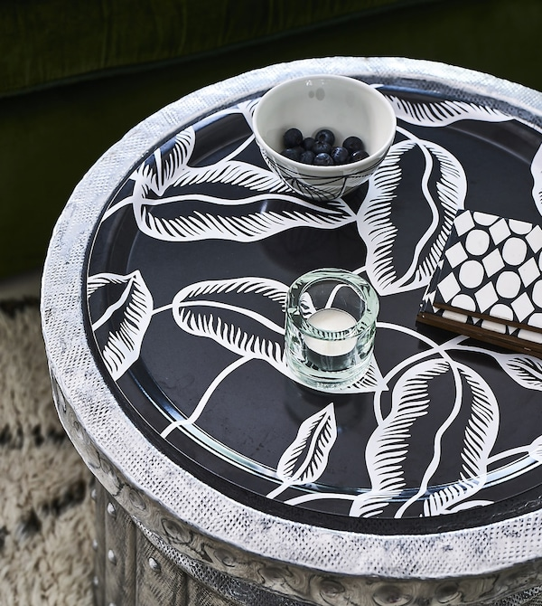A candle and bowl on a tray, with a black and white motif.
