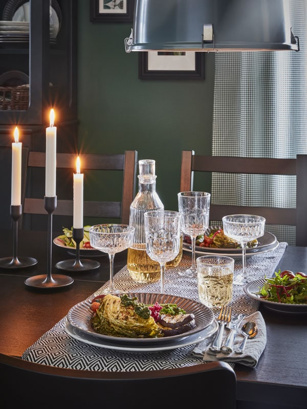 A candle lit dinner set on a dining room table.