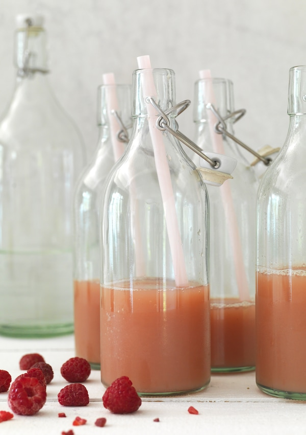 A carafe of a drink with fresh fruit and herbs is next to an open bottle of KORKEN, a refreshing elderflower syrup.