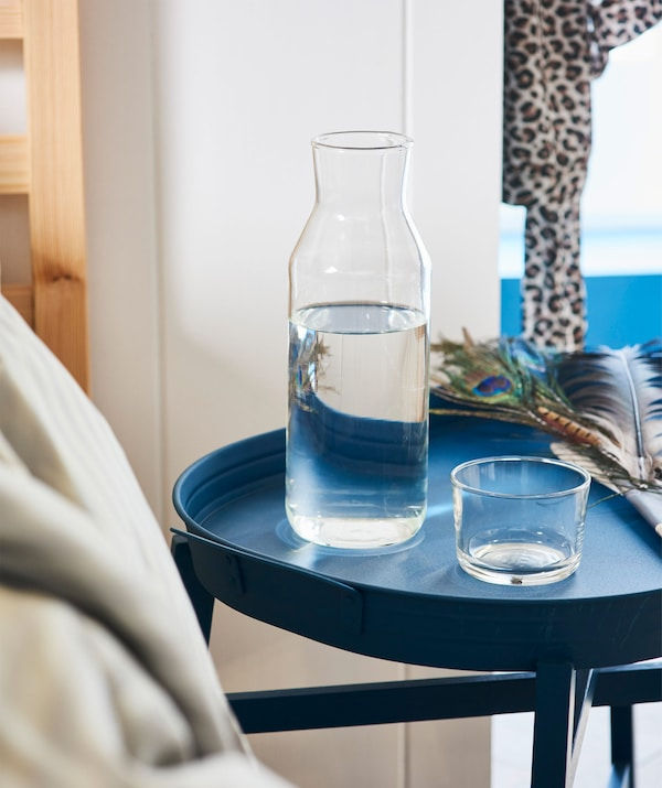 A carafe of water on a blue tray table next to a bed