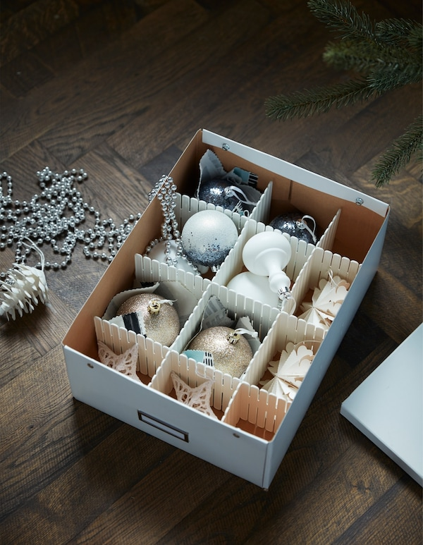 A cardboard box, with compartments, filled with holiday decorations.