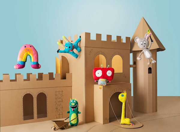 A cardboard castle in front of a blue sky background with several colorful soft toys positioned around the castle.