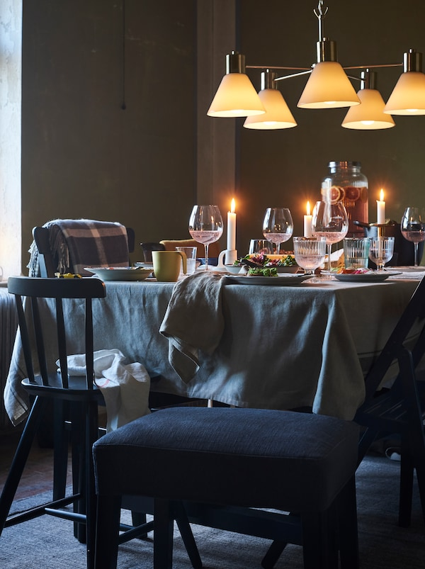 A ceiling lamp hangs over a dining table set for an informal meal. A black stool offers extra seating.
