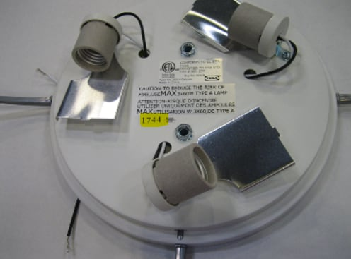 A ceiling lamp without the shade, exposing the three electrical bulb sockets.