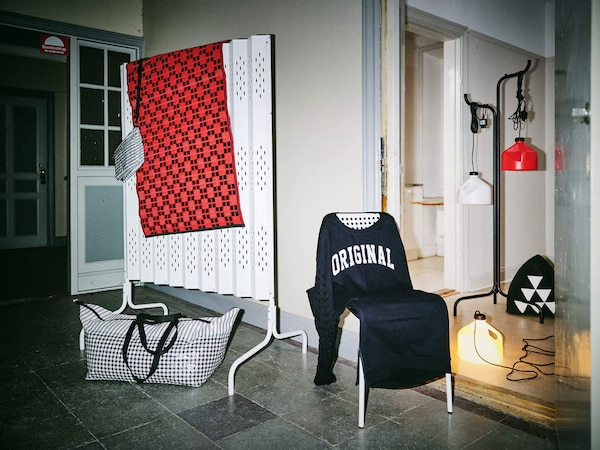 A chair draped with a dark shirt that says ORIGINAL on it, and a white room divider behind it with a red rug draped over it.