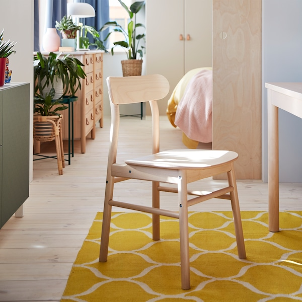 A chair in birch stands on a yellow rug. A chest of drawers in birch and green plants stand in a room in the background.