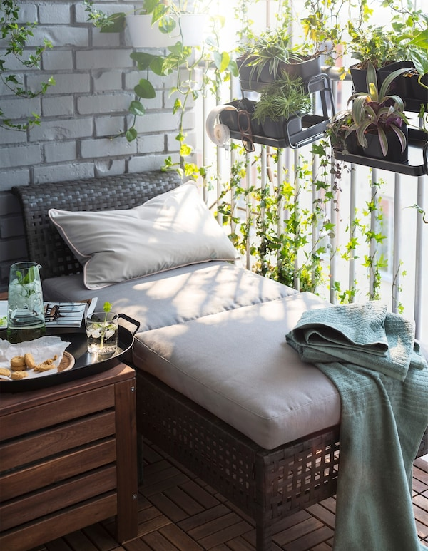 A chaise lounge on a balcony surrounded by plants.