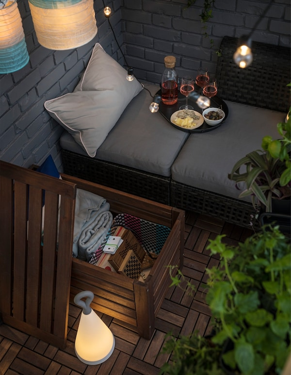 A chaise lounge on a balcony with an open IKEA ÄPPLARÖ storage bench, revealing board games and cushions.