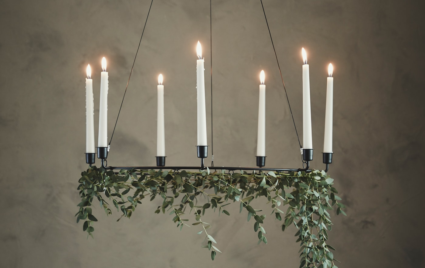 A chandelier with candles and ivy hanging off of it
