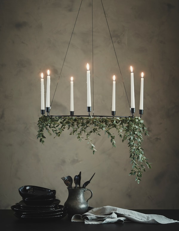 A chandelier with some fresh-cuts flowers hanging beneath the candles, above a side table topped with serverware.