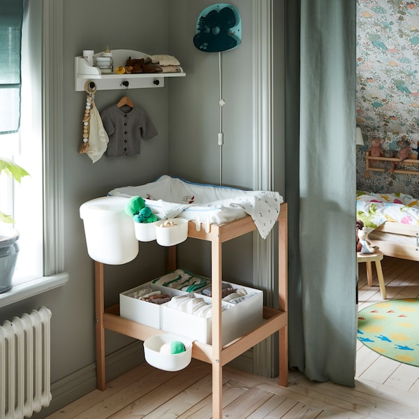 A changing table with accessories in a bedroom. A window on one side, an alcove doubling as a children's room on the other.