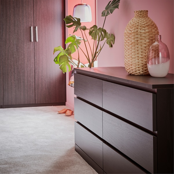 A chest of drawers and a wardrobe in black-brown, a grey rug, a glass vase, and a green plant.
