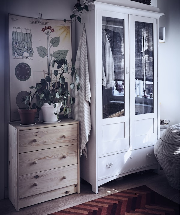 A chest of drawers and wardrobe in a hallway, with plants and a wall hanging above the chest.