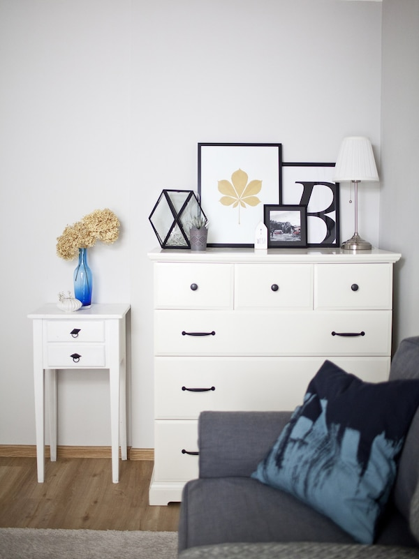 A chest of drawers with picture frames on top.