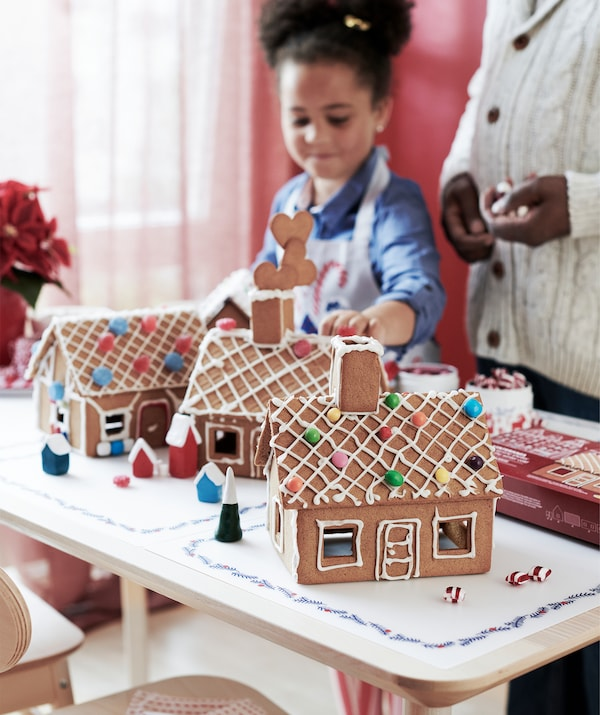 A child and an adult standing by a table on which is placed several finished gingerbread houses neatly decorated with icing.