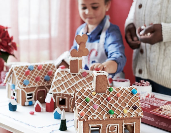 A child building three VINTERSAGA oven-baked gingerbread houses, decorated with icing and sweets.