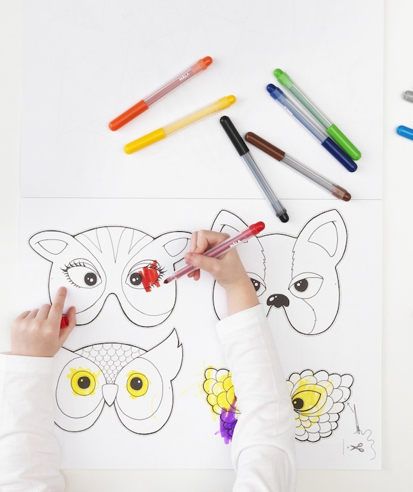 A child coloring in animal-shaped masks in a book.