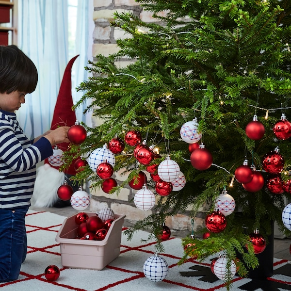 A child decorating a Christmas tree with a mixture of red and white VINTERFEST decorative ornaments.