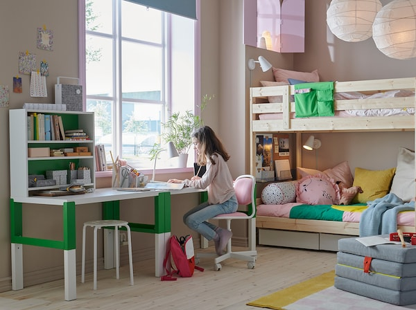 A child doing homework in a dedicated study space that includes a desk with shelves, chair, and lamp.