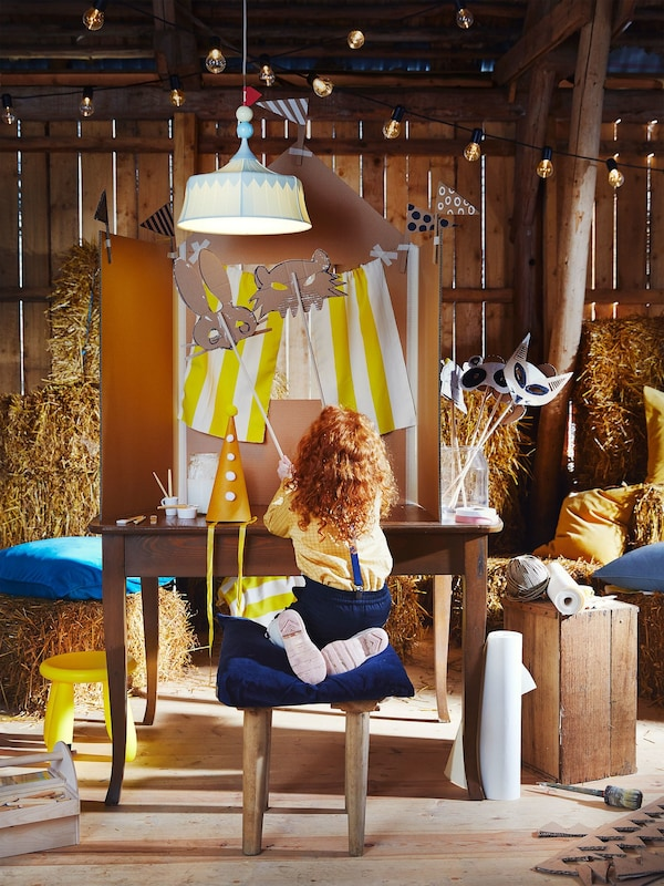 A child has created a cardboard puppet show in a barn surrounded by straw bales and illuminated by a blue TROLLBO pendant lamp.