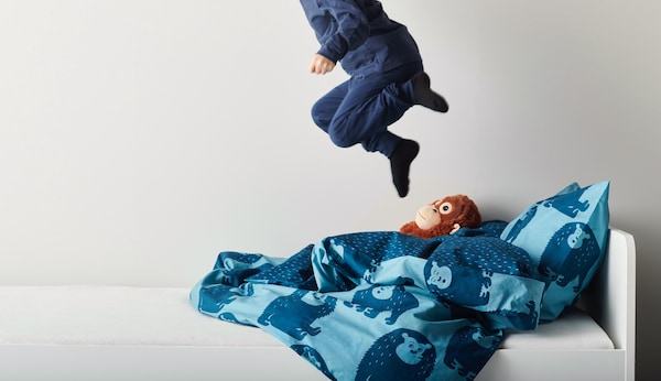 A child in blue pajamas is jumping on the bed.