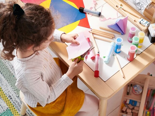 A child is cutting pink paper while sitting on a kid's chair next to a table filled with colourful MÅLA paint and paper.