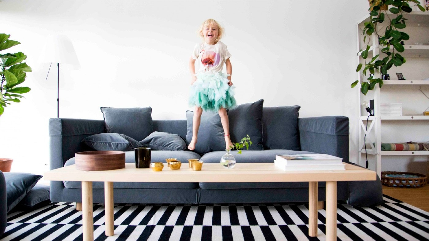 A child jumping on a blue sofa in a living room with a black and white striped rug and long wood coffee table.
