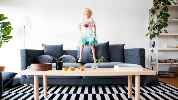 A child jumps on a grey sofa in a living room with a black-and-white striped rug on the floor