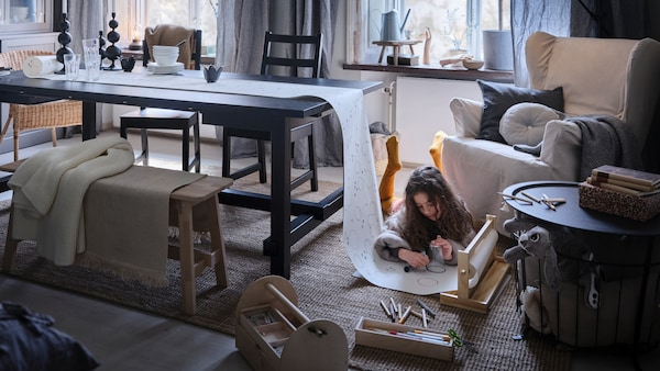 A child lies on a rug on the floor drawing on a roll of paper which has one end on a black NORDVIKEN extendable table.