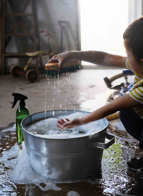 A child lifts a wet wooden brush from a metal bucket of soapy water.