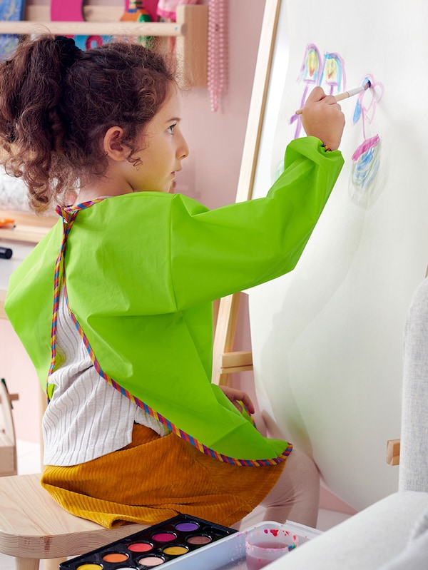 A child painting on a large sheet of paper.