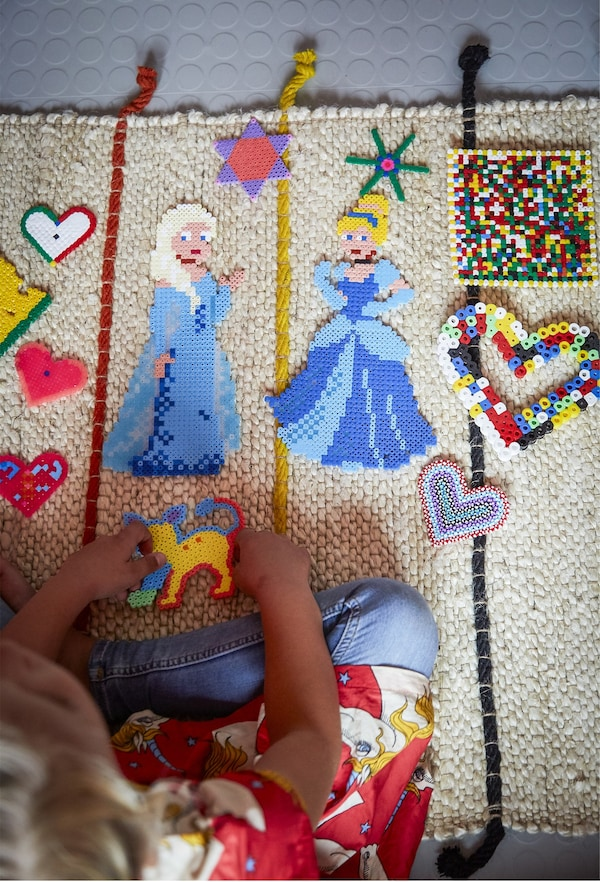 A child playing with soft toys on a colourful rug.