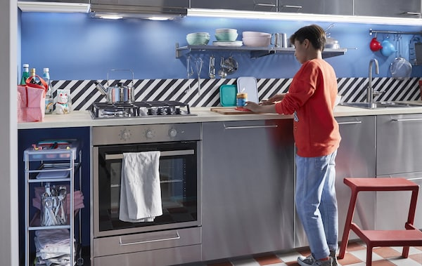 A child preparing a snack in a stainless steel kitchen with shelves and a step stool.