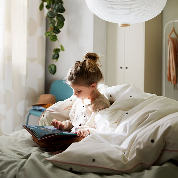 A child reading a book, ensconced in a cozy bed with a green-striped BERGPALM  duvet cover.