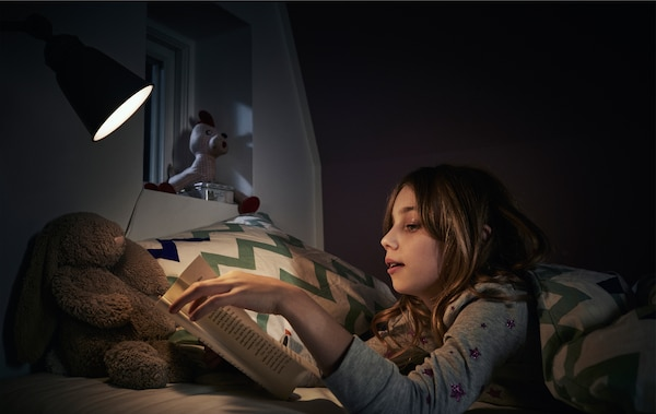 A child reading a book in bed with a reading lamp.