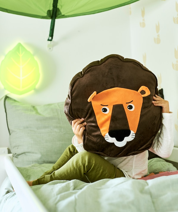 A child sits on a bed under a leaf-shaped canopy holding a cushion in the shape of a lion in front of their face.
