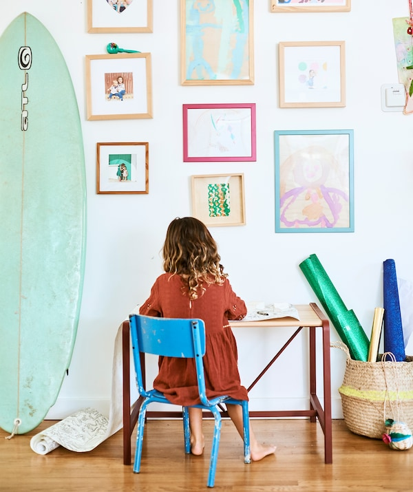 A child sits on a blue chair at a small desk, against a wall of children's paintings and family photographs next to a surfboard.
