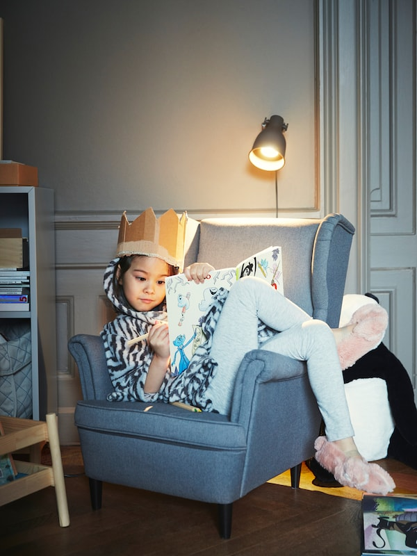 A child wearing a toy crown lounges in a grey STRANDMON children's armchair under a wall lamp and draws in a book.