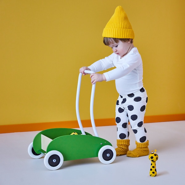 A child wearing a yellow hat and black and white spotty trousers pushes a green MULA toddle truck past a soft toy.
