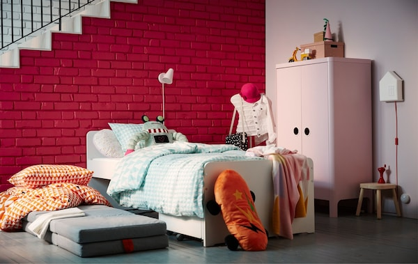 A children's bedroom area with a bed, a pink wardrobe and two stacked mattresses on the floor.