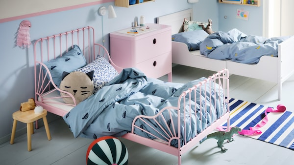 A children's bedroom with a light pink MINNEN extendable bed and a white bed made with blue VÄNKRETS and BARNDRÖM bedding.