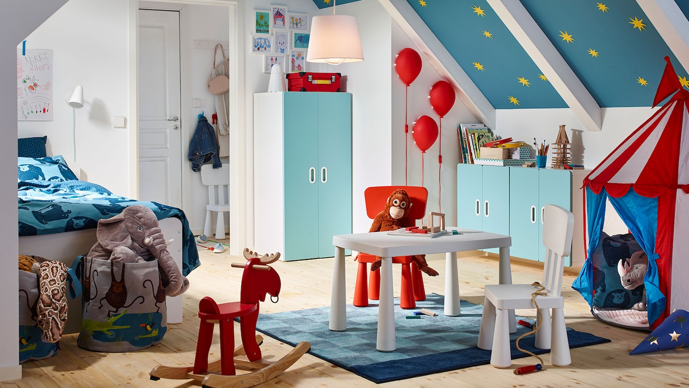 A children's bedroom with a light pink MINNEN extendable bed with slatted bed base, white desk, books and soft toys.