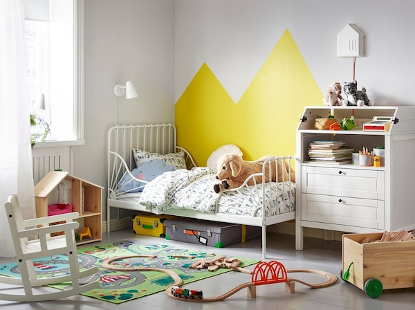 A children's bedroom with an IKEA MINNEN white extendable bedframe and SUNDVIK white changing table.