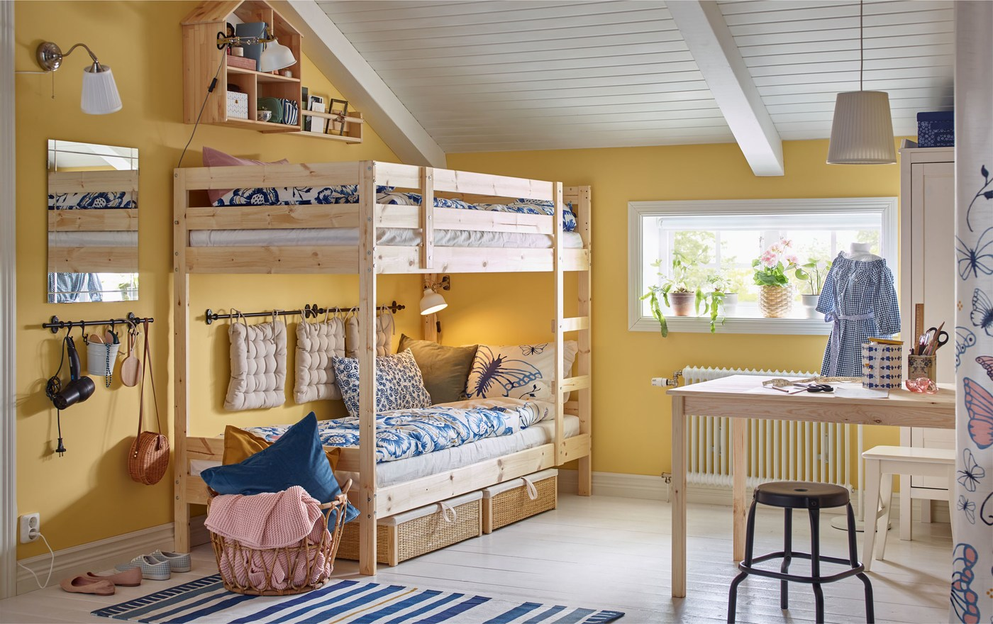 A children's bedroom with an IKEA MYDAL bunk bed in pine, a work desk, a NÄPEN white clothes stand and stools.