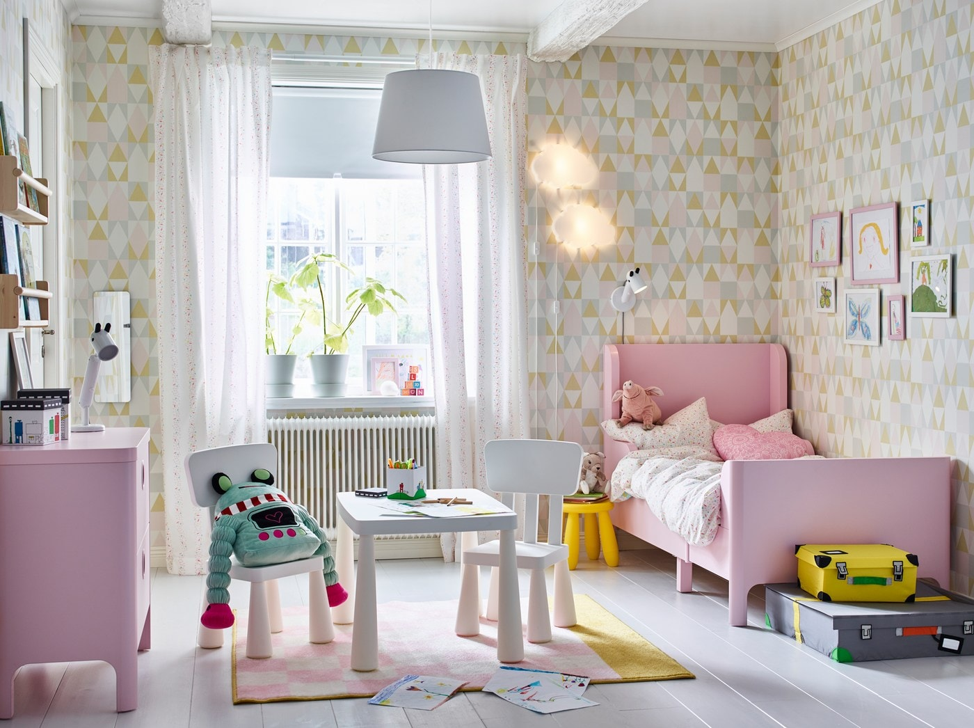 A children's bedroom with patterned wallpaper in muted tones has a pink extendable BUSUNGE bed and a table with chairs.
